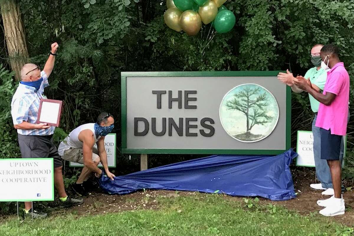John Bollenbecker reveals a covering and unveils the entrance sign to The Dunes neighborhood, which he recently rebuilt (Paul Grondahl / Times Union)