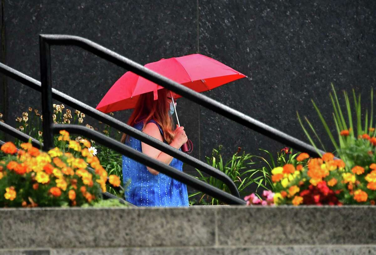 A woman walks down stairs in front of a building on Washington Ave. with an umbrella during a rainstorm on Tuesday, Aug. 4, 2020 in Albany, N.Y. Heavy rains due to Tropical Storm Isaias are expected this afternoon into the evening with possible flooding. (Lori Van Buren/Times Union)