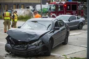 Midland firefighters and police secure the scene of a collision involving three vehicles at the intersection of Cronkright and Buttles Tuesday, Aug. 4, 2020 in Midland. (Katy Kildee/kkildee@mdn.net)