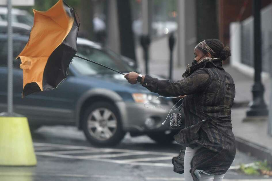 A pedestrian struggles with her umbrella as tropical storm Isaias brings heavy wind and rain to Greenwich, Conn. Tuesday, Aug. 4, 2020. The National Weather Service issued a tropical storm warning, flash flood watch, and tornado watch as the storm passed through Connecticut.