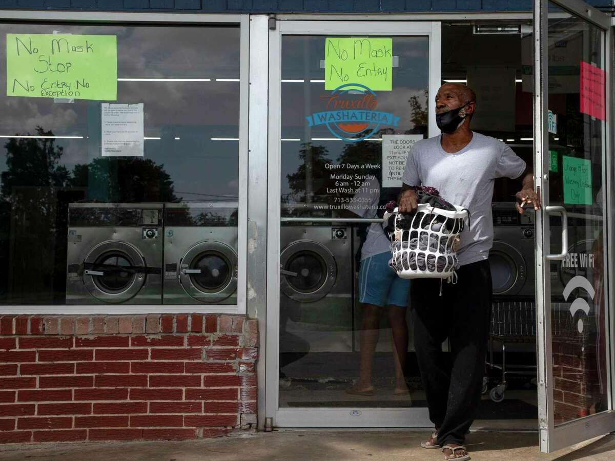 Wade Dix, 64, enters Truxillo Washateria with a load of clothes Thursday, July 30, 2020, in Houston. People who depend on change for things like laundry are finding it hard to find change during the ongoing national coin shortage.