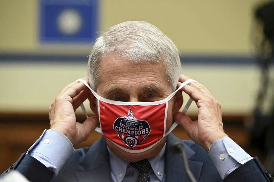 WASHINGTON, DC - JULY 31: Anthony Fauci, director of the National Institute of Allergy and Infectious Diseases, removes his Washington Nationals protective mask during a House Select Subcommittee on the Coronavirus Crisis hearing on July 31, 2020 in Washington, DC. Trump administration officials are set to defend the federal government's response to the coronavirus crisis at the hearing hosted by a House panel calling for a national plan to contain the virus. (Photo by Erin Scott-Pool/Getty Images) ***BESTPIX*** Photo: Pool / Getty Images / 2020 Getty Images