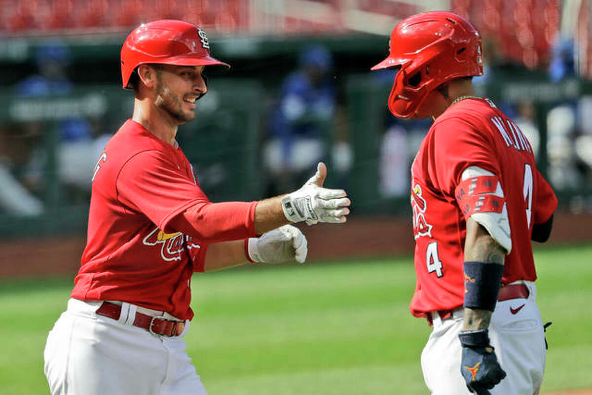 The Cardinals' Paul DeJong (left) is congratulated by teammate Yadier Molina after DeJong's homer during a July 22 exhibition game against the Kansas City Royals in St. Louis. The Cardinals announced Tuesday that DeJong and Molina are among six of the players who have tested positive for coronavirus.