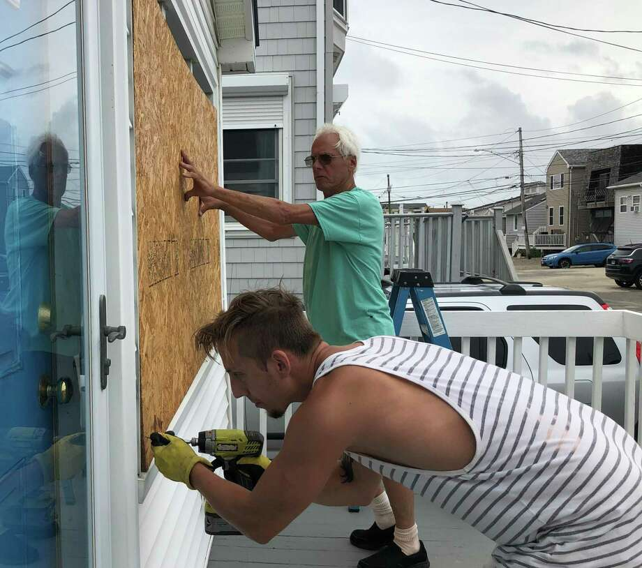Ian Wahlberg screws a piece of plywood held by his father, Tom Wahlberg, into a house on Stratford's Beach Drive Tuesday morning before Tropical Storm Isaias was forecast to hit the region. Photo: Ethan Fry / Hearst Connecticut Media