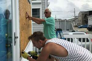 Ian Wahlberg screws a piece of plywood held by his father, Tom Wahlberg, into a house on Stratford's Beach Drive Tuesday morning before Tropical Storm Isaias was forecast to hit the region.