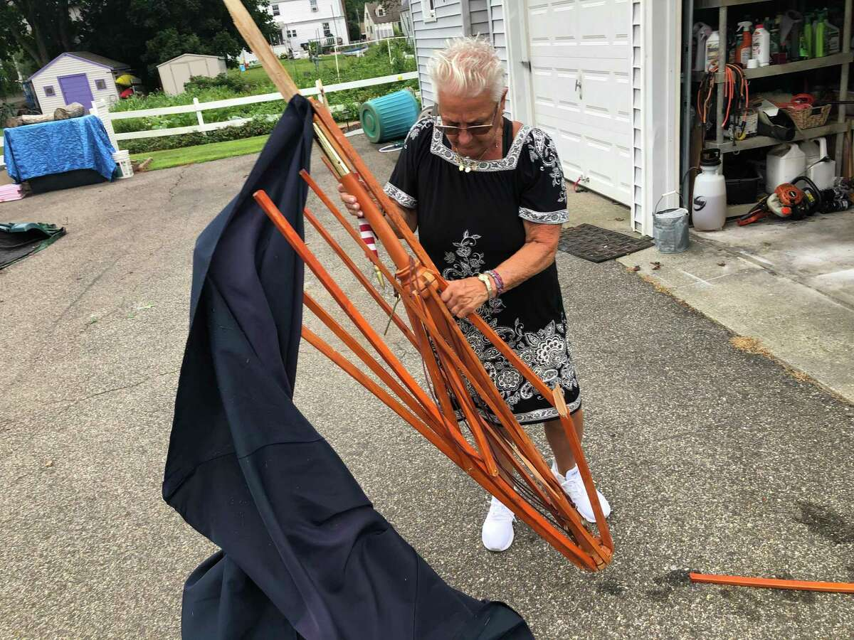 While preparing Tuesday ahead of Tropical Storm Isaias, Stratford resident Natalie Terentieff looks at an umbrella damaged by high winds Monday night in the driveway of her home in Lordship.