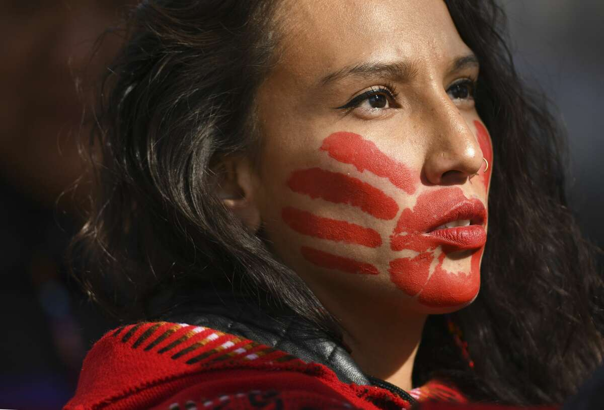 A woman has a painted red hand over her mouth to show solidarity for missing and murdered indigenous, black and migrant women and children during a rally in 2019.