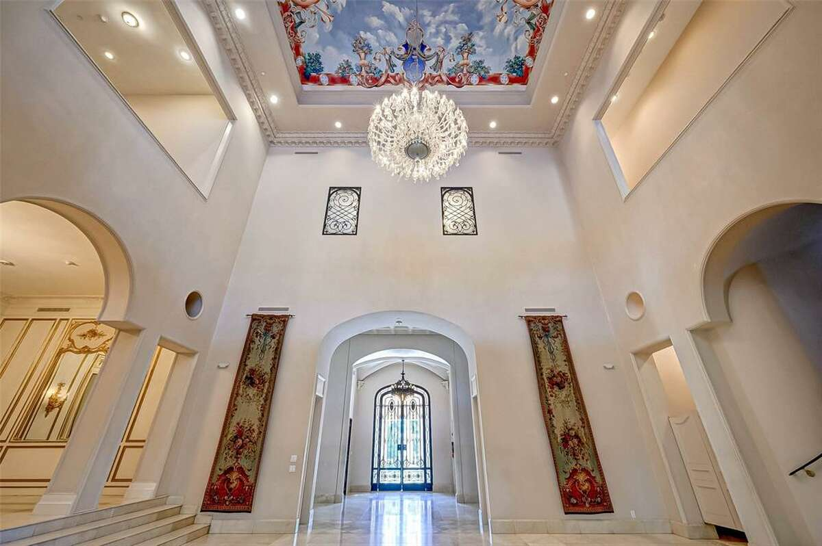 A grand foyer features a large chandelier at its center.