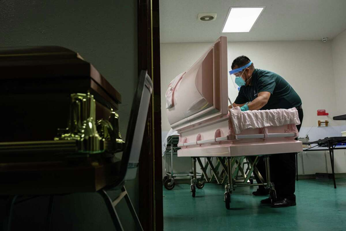 A worker prepares a casket at a funeral home in Brownsville. A University of Texas at Austin model projects that 15,000 more Texans will die of COVID-19 by the end of August. On Monday, however, researchers behind the alarming projection said they are working to correct an erroneous data point that skewed the model's conclusions.