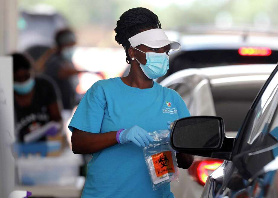A woman brings testing supplies to a patient for a self-administered coronavirus test at Pridgeon Stadium, one of Harris County Public Health's eight coronavirus testing sites, Friday, July 31, 2020, in Cypress. Photo: Jason Fochtman, Houston Chronicle / Staff Photographer / 2020 © Houston Chronicle