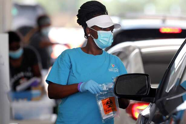 A woman brings testing supplies to a patient for a self-administered coronavirus test at Pridgeon Stadium, one of Harris County Public Health's eight coronavirus testing sites, Friday, July 31, 2020, in Cypress.