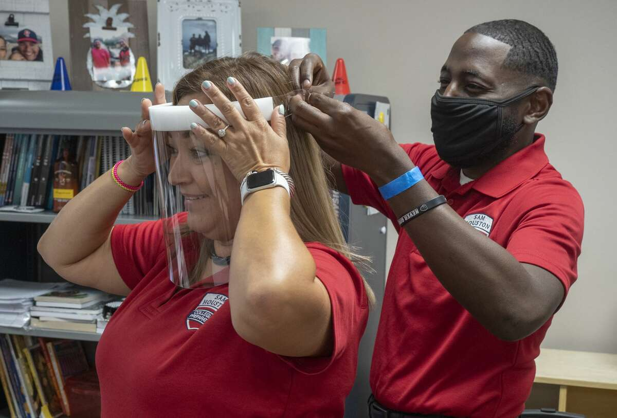 Brandon Thurston, chancellor of Sam Houston Collegiate Preparatory, helps Gabriela Aguilar with a face mask teachers may wear as they prepare for the first day of classes in this file photo from 2020 at Sam Houston Collegiate Preparatory. Tim Fischer/Reporter-Telegram