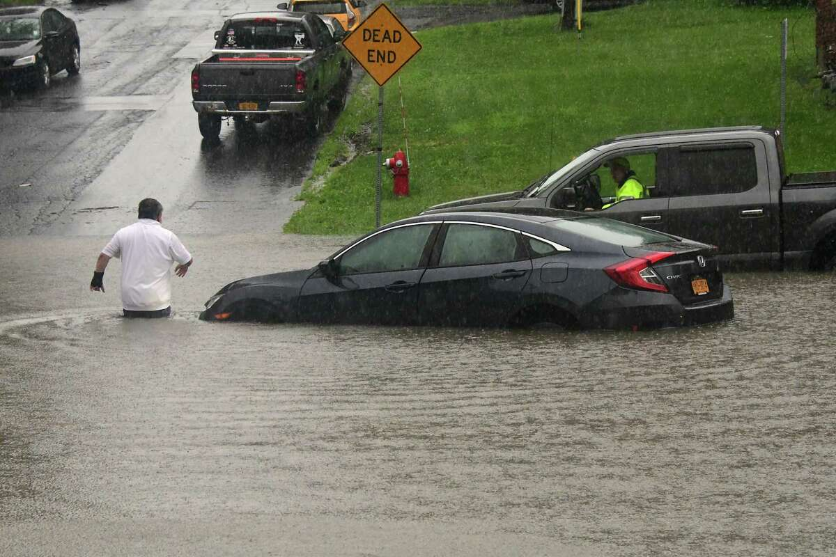 A driver evacuates his car after trying to drive through a flooded part of Hacket Blvd. near Crown Terr. and getting stuck on Tuesday, Aug. 4, 2020 in Albany, N.Y. Heavy rains due to Tropical Storm Isaias brought flooding to the area.