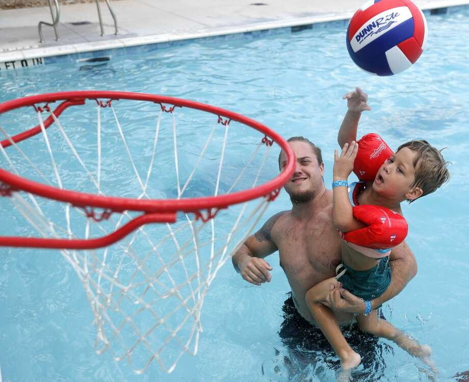 Benjamin Prestridge shoots a basket has his dad, Dylan, holds him up during a visit to Conroe's new $5.6 million waterpark opened to the public, Wednesday, Aug. 4, 2020, in Conroe. The waterpark is opened daily from 11:00 a.m. to 6:00 p.m. features a children's pool, playground, a youth-adult pool and five water slides. Tickets are $8 per person with visitors allowed to bring coolers and food. Photo: Jason Fochtman/Staff Photographer / 2020 © Houston Chronicle