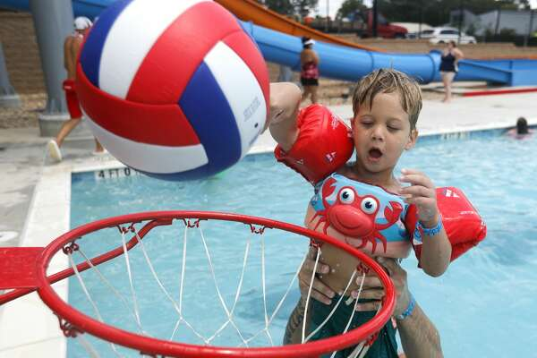 Benjamin Prestridge shoots a basket has his dad, Dylan, holds him up during a visit to Conroe's new $5.4 million waterpark opened to the public, Wednesday, Aug. 4, 2020, in Conroe. The waterpark is opened daily from 11:00 a.m. to 6:00 p.m. features a children's pool, playground, a youth-adult pool and five water slides. Tickets are $8 per person with visitors allowed to bring coolers and food.