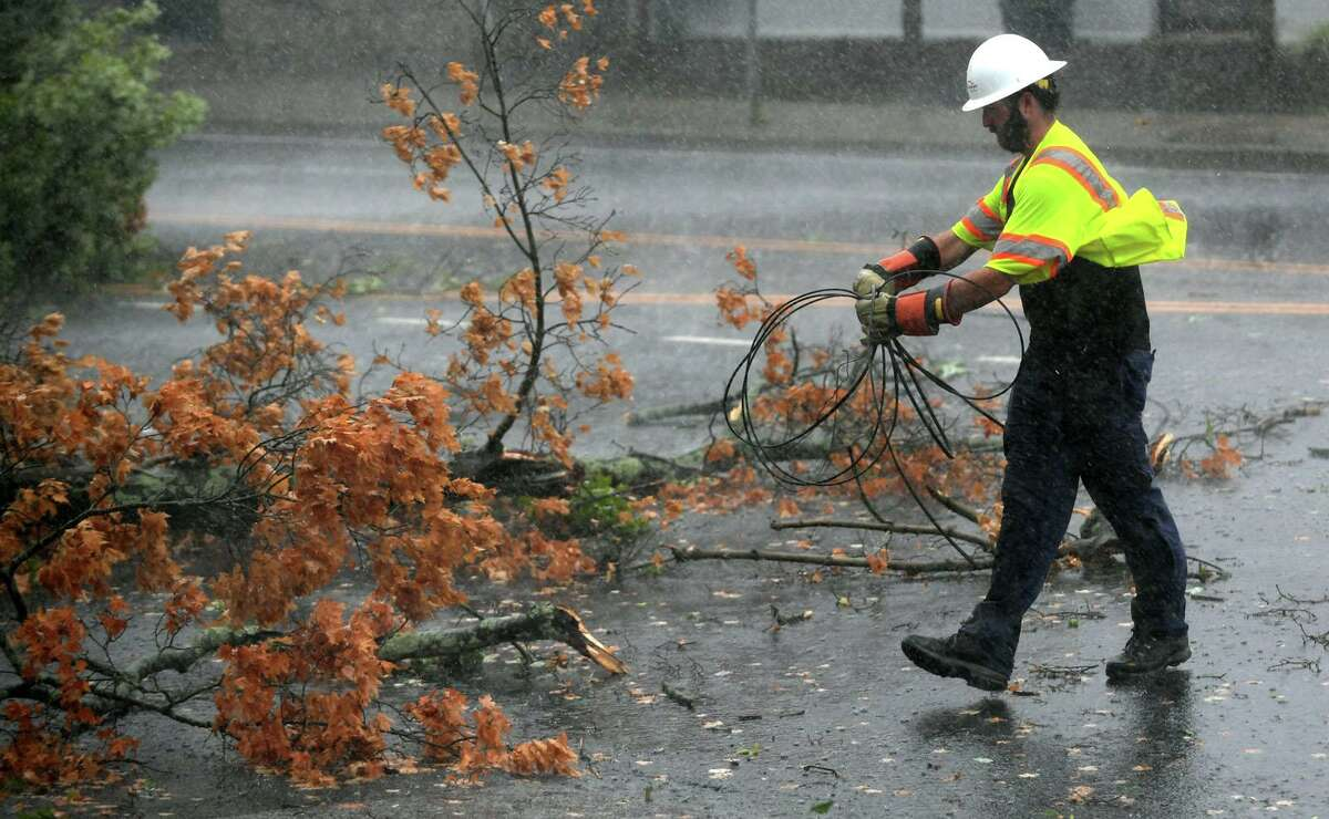 A utility worker clears wires as a fallen tree limb blocks a portion of Main Avenue in Norwalk during Tuesday's tropical storm.