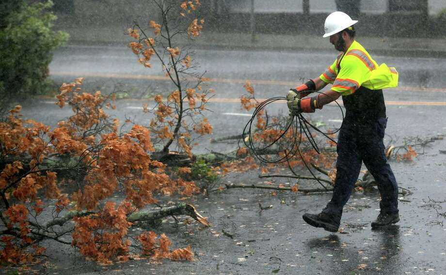 A utility worker clears wires as a fallen tree limb blocks a portion of Main Avenue in Norwalk during Tuesday's tropical storm. Photo: Erik Trautmann / Hearst Connecticut Media / Norwalk Hour