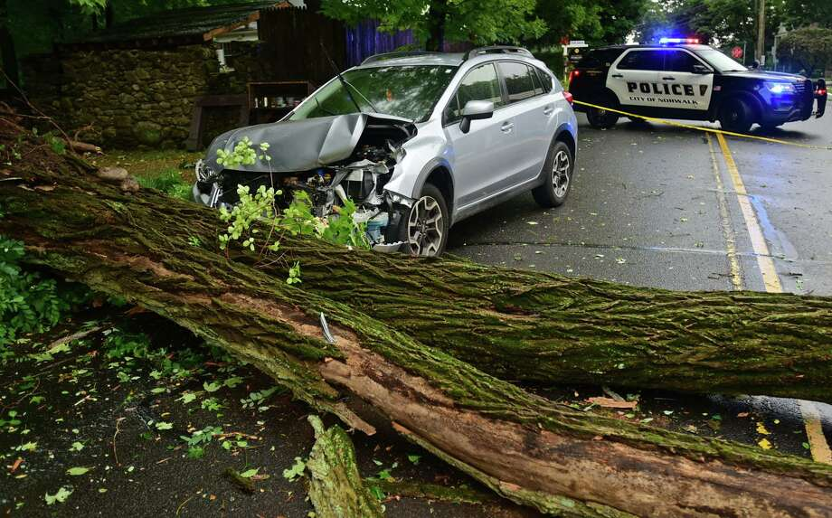 A car was struck by a fallen tree limb while wind gusted up to 70 miles per hour as Tropical storm Isaias brings heavy rain Tuesday, August 4, 2020, to Norwalk, Conn. Photo: Erik Trautmann / Hearst Connecticut Media / Norwalk Hour