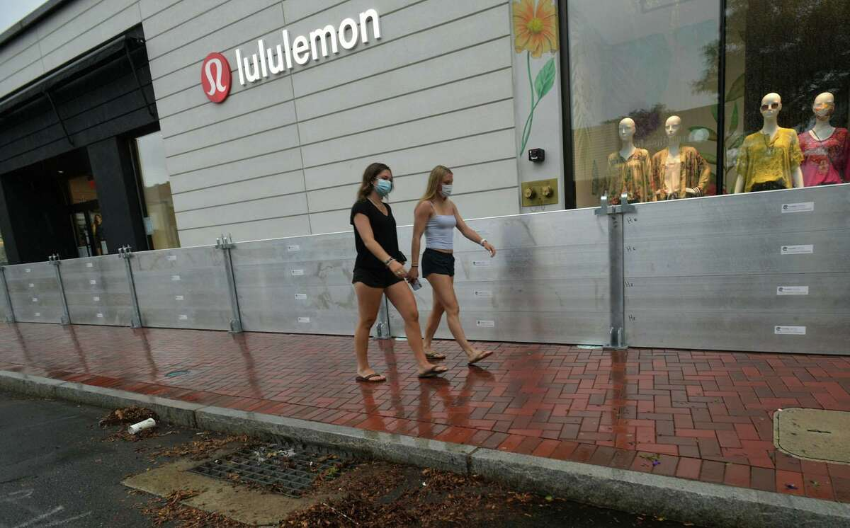 Pedestrians stroll by flood barriers on Main Street in Westport, Conn., in August 2020 in advance of Tropical Storm Isaias.