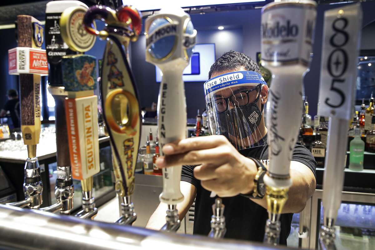 A bartender pours a beer while wearing a mask and face shield amid the coronavirus pandemic at Slater's 50/50 Wednesday, July 1, 2020, in Santa Clarita, Calif. According to a new poll, Americans overwhelmingly are in favor of requiring people to wear masks around other people outside their homes, reflecting fresh alarm over spiking infection rates. The poll also shows increasing disapproval of the federal government's response to the pandemic. California is among the states seeing the greatest surge in cases now. (AP Photo/Marcio Jose Sanchez, File)