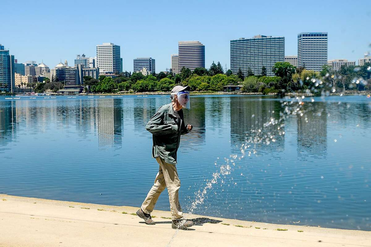 A jogger wears a face shield while exercising at Lake Merritt on Tuesday, May 26, 2020, in Oakland, Calif.