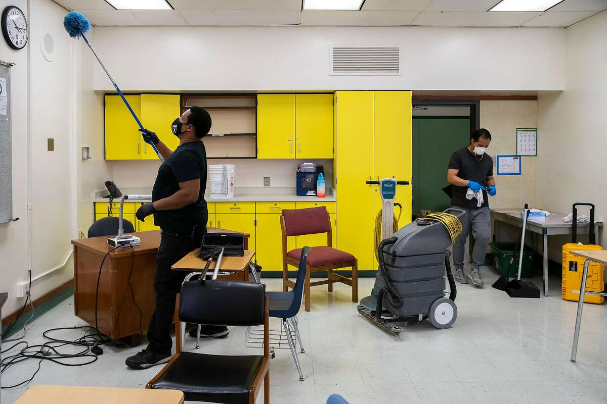 From left: Philip Elliott, the supervising custodian, and custodian Orlando Lavarias clean and sanitize a classroom that will have tables and chairs set up for physical distancing at Westlake Middle School on Friday, July 10, 2020, in Oakland, Calif. Schools are planning on how to reopen in the fall to ensure the safety and wellbeing of students and staff, amid the coronavirus pandemic. The middle school also holds the MetWest High School Ericka Huggins Campus. The COVID-19 pandemic has led to a record one-year enrollment drop of 155,000 students, according to state projections, out of 6 million.