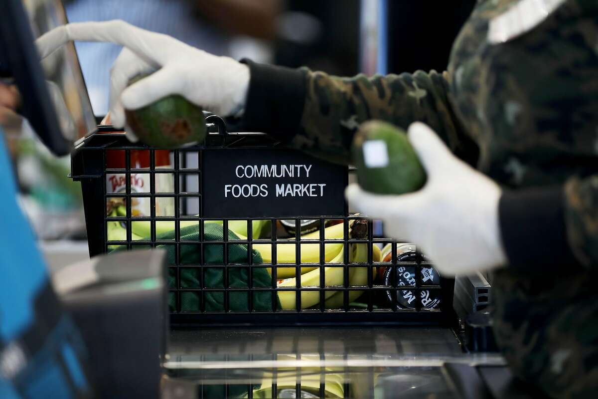 Sharon Rance, an employee at Community Foods Market, checks out a customer at the store located at 3105 San Pablo Ave., on Thursday, April 2, 2020, in Oakland, Calif.