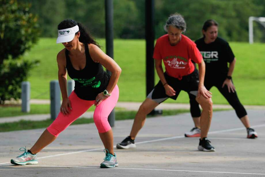 Team Green Running member Marie Notargiacomo, left, stretches in front of Kimberly Dufford and Susan Soulant before a workout at Terramont Park, Tuesday, Aug. 4, 2020, in The Woodlands. Photo: Jason Fochtman, Houston Chronicle / Staff Photographer / 2020 © Houston Chronicle