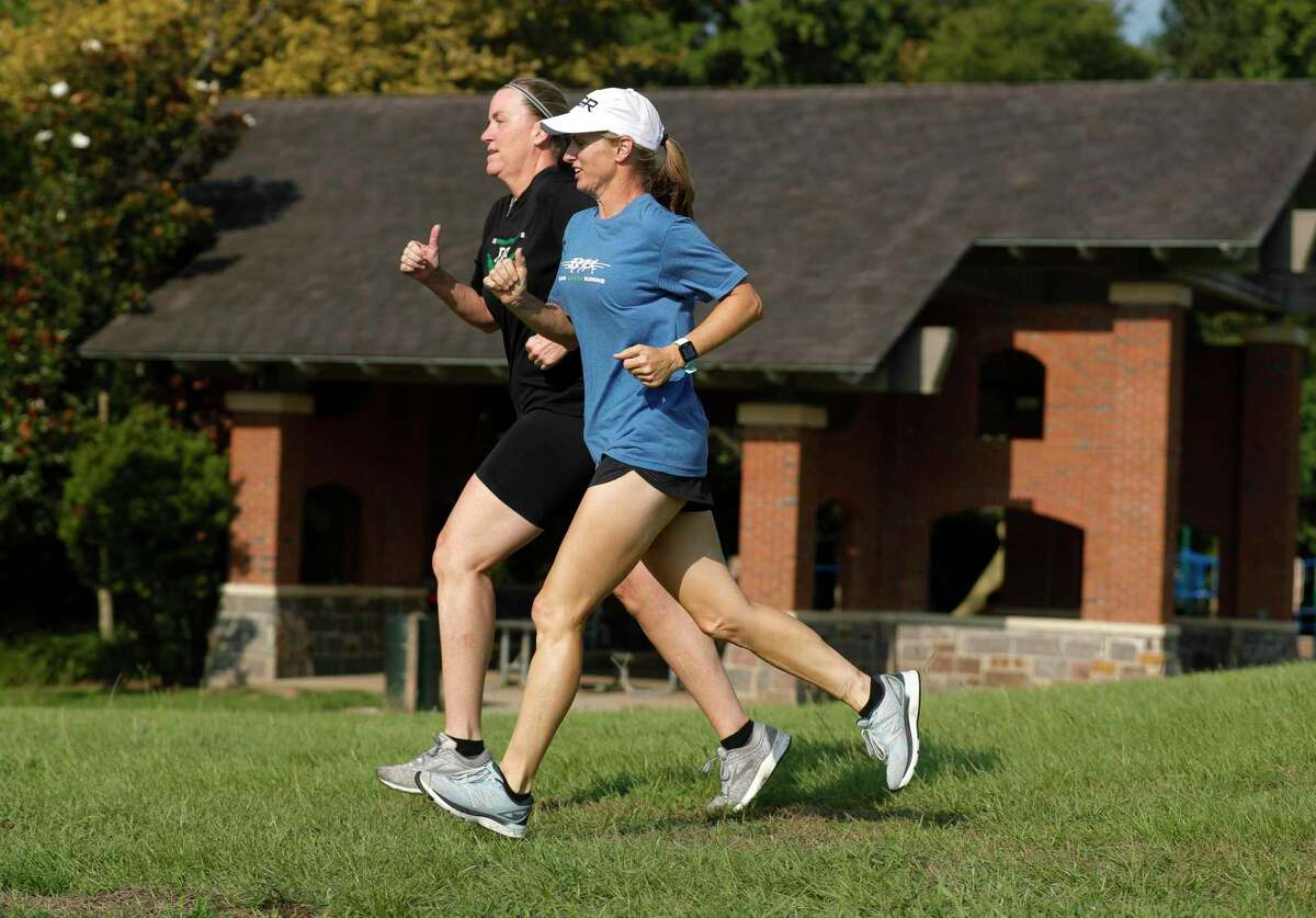 Team Green Running member Elizabeth Ryan, right, runs beside Holly Wright as they take part in a workout at Terramont Park, Tuesday, Aug. 4, 2020, in The Woodlands.