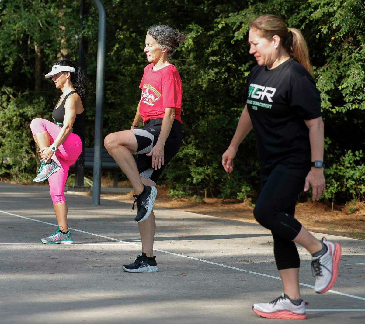 Team Green Running member Anne Marie Notargiacomo, far left, stretches beside Kimberly Dufford and Susan Soulant before taking part in a workout at Terramont Park, Tuesday, Aug. 4, 2020, in The Woodlands.
