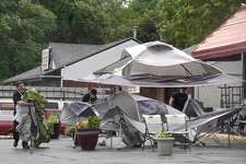 Workers remove tents from the front of the Holiday Diner during tropical storm Isaias Tuesday, August 4, 2020, in Danbury, Conn.