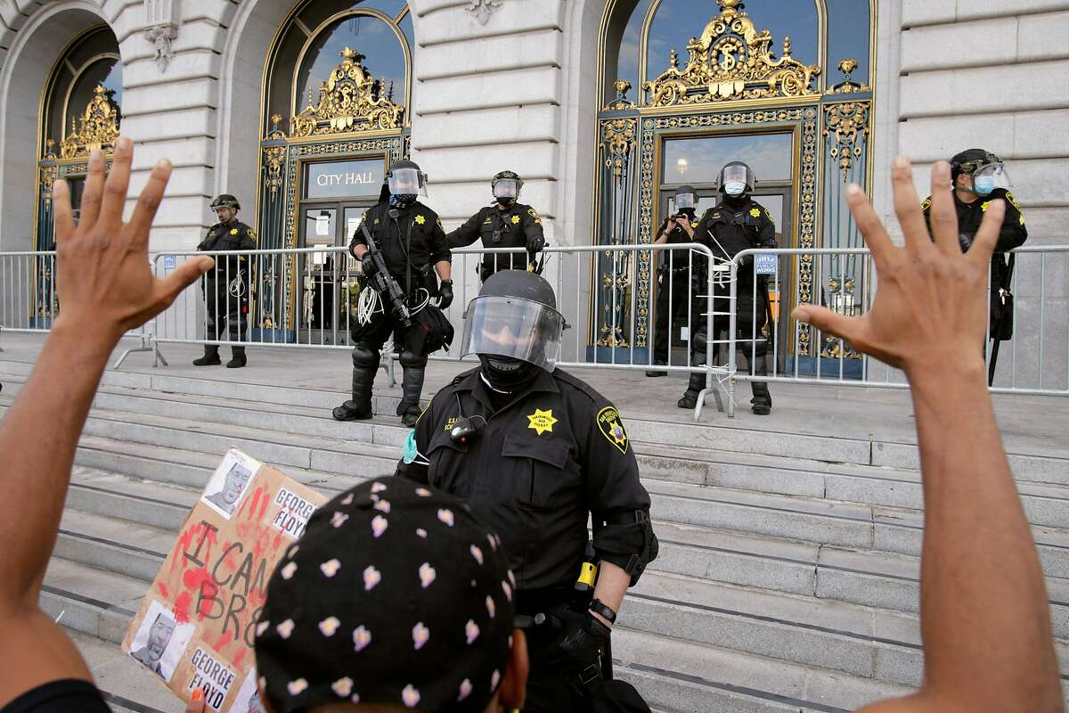 A row of San Francisco Sheriffs officers watch as a protester puts his hands up as thousands gathered at City Hall in San Francisco, Calif., on Sunday, May 31, 2020, for the third straight night of worldwide solidarity protests over the killing of George Floyd in Minneapolis by police earlier in the week.