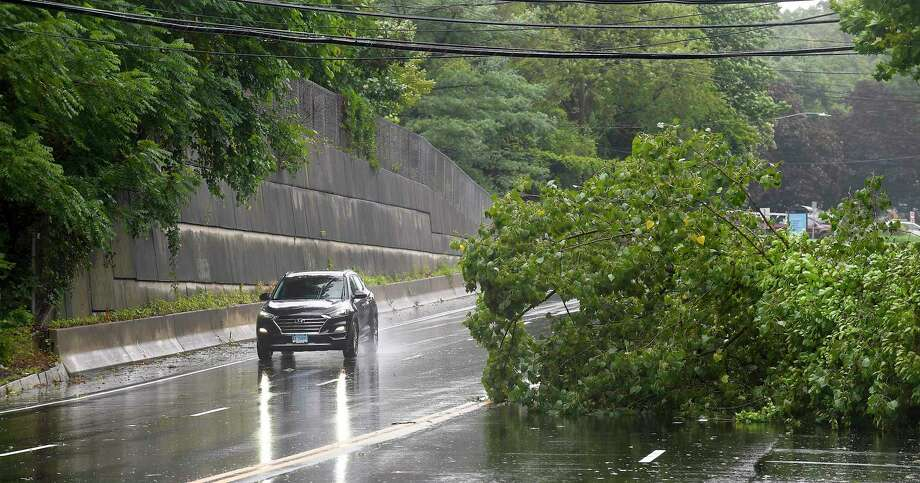 A motorist passes by a fallen tree on Long Ridge Road on August 4, 2020 in Stamford, Connecticut. Photo: Matthew Brown / Hearst Connecticut Media / Stamford Advocate