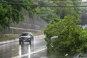 A motorist passes by a fallen tree on Long Ridge Road on August 4, 2020 in Stamford, Connecticut.