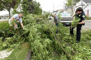 Branford, Connecticut - Tuesday, August 04, 2020: John Groves of Branford, left, Joe Velardi of Guilford, center, and Branford police Sgt. Chris Romanelli, right, work together to clear debris from downed tree that blocked a lane on Maple Street in Branford during Tropical Storm Isaias.