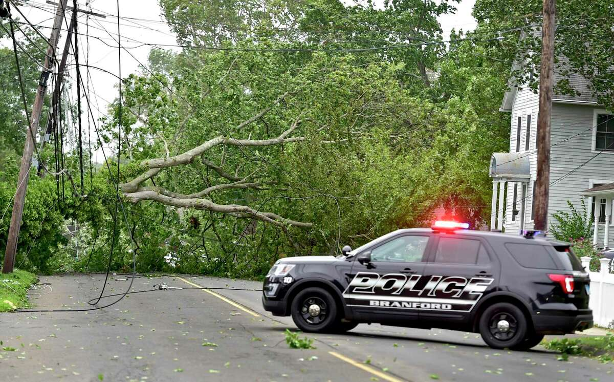 A Branford police vehicle blocks Maple Street near downed power lines and a tree that came down because of Tropical Storm Isaias Aug. 4, 2020.