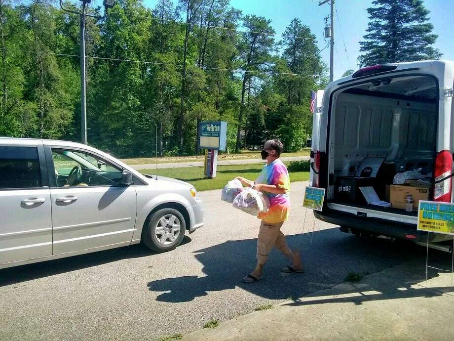 A family receives meals at Wellston Elementary through the summer feeding program. (Courtesy photo)
