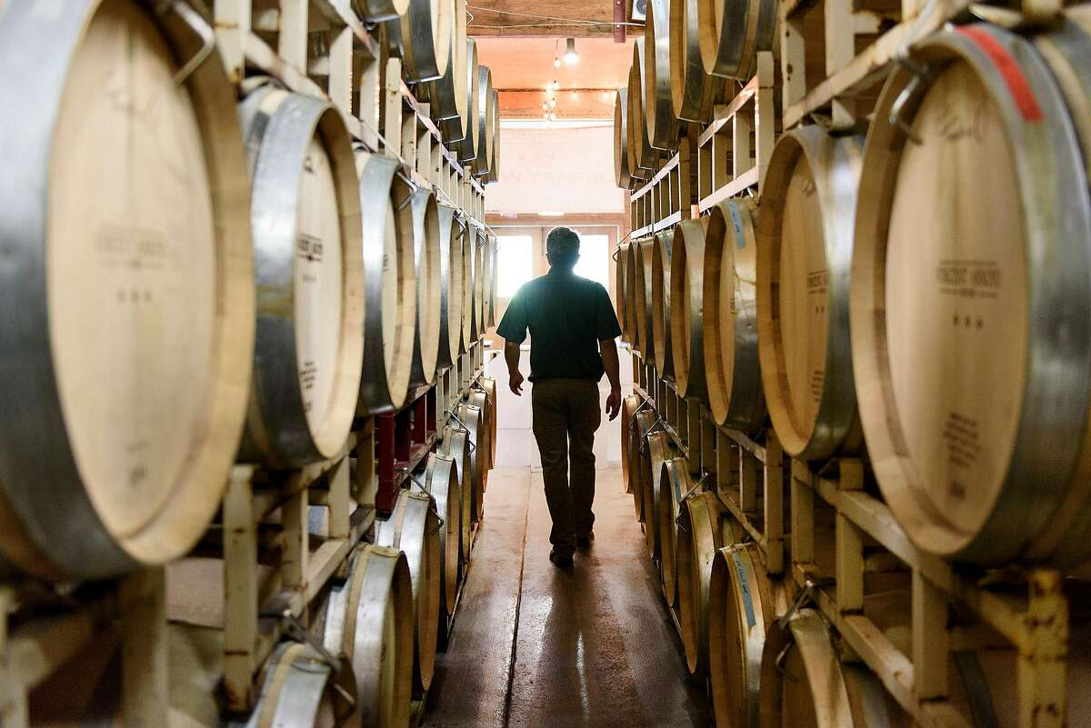 Host Teddy Wiebe walks between stacks of barrels at Vincent Arroyo Winery in Calistoga, Calif., on Friday July 20, 2018.