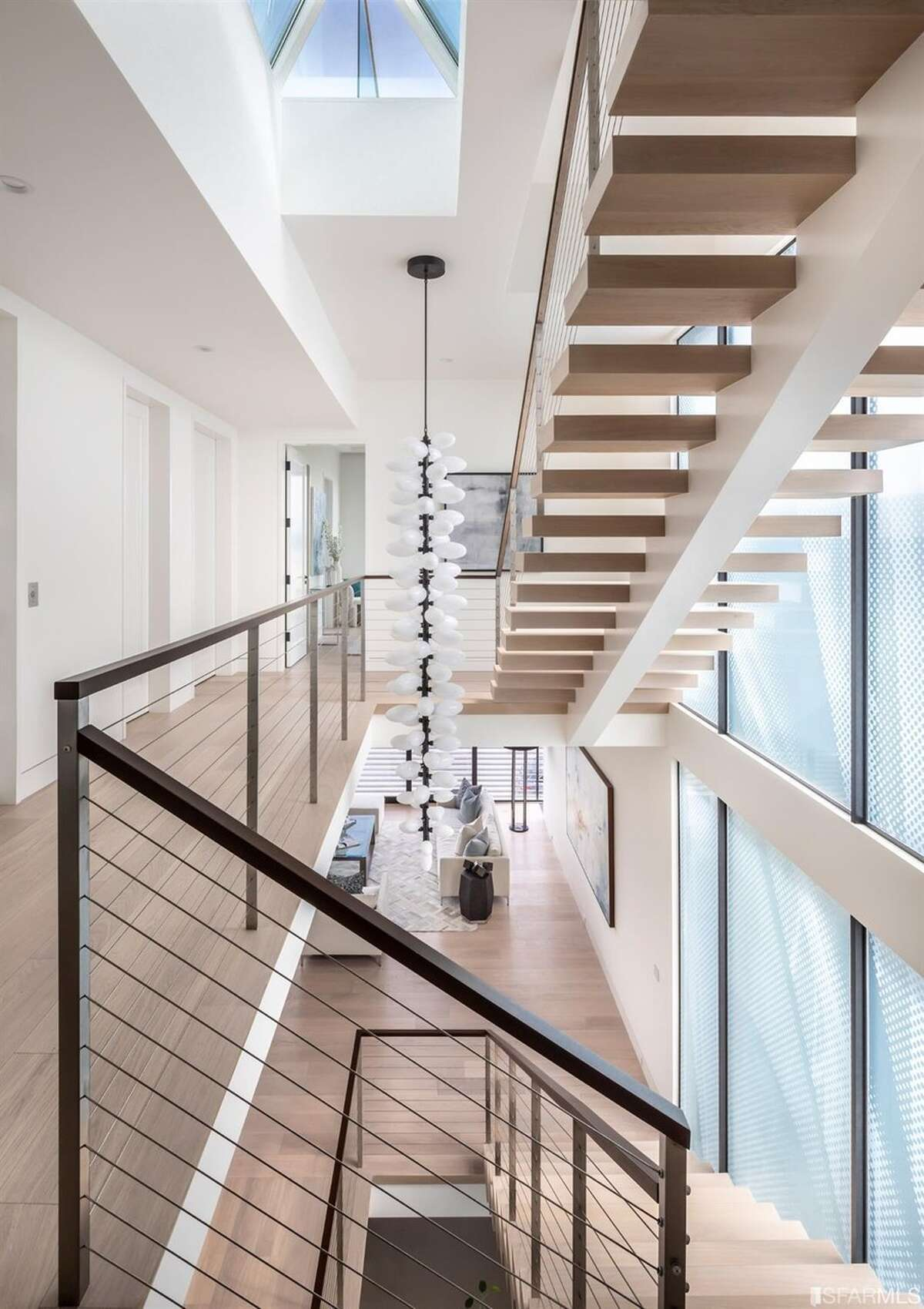 """The floors are connected via this light-filled stairway, though the home also has an elevator. But given that the five-bedroom, 7.5-bath property has over 7,000 square feet, it's remarkable that it only has three levels of indoor space, said Moshayedi. """"Most comparable homes in the city are much more vertical in the design, while this home has very large floor plates on each level due to the lot size,"""" she explained."""