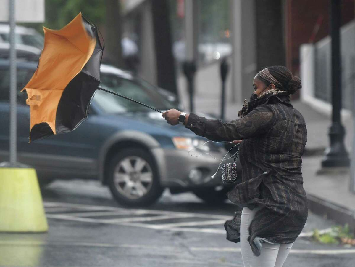 A pedestrian struggling with her umbrella in Greenwich, Conn., taken on Aug. 4, 2020. Southern Connecticut will be under a wind advisory from 8 p.m. March 12, 2021, through 6 a.m. March 13.