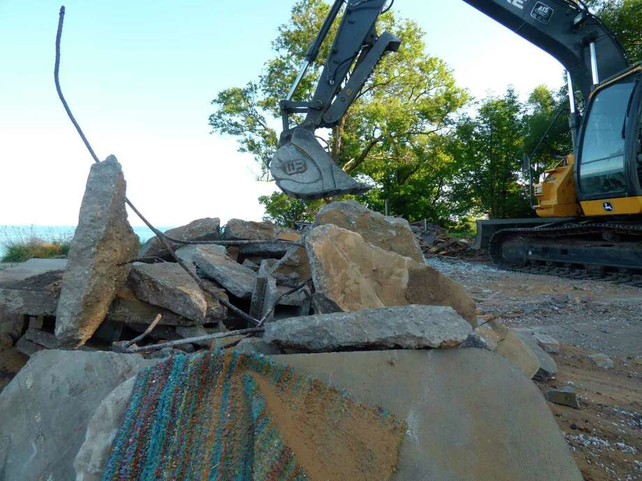 Shoreline erosion threatened to topple a home on Merkey Road into Lake Michigan. On Tuesday, excavators were brought into to demolish the structure. (Scott Fraley/ News Advocate)
