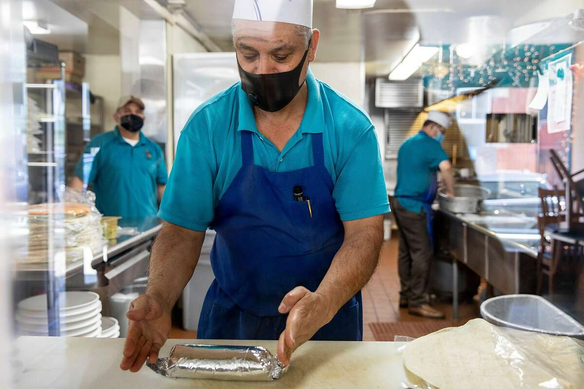 Rosendo Carlos Valdez works to wrap a burrito for a customer at Ramiro & Sons Taqueria in Alameda, Calif. Tuesday, August 4, 2020.