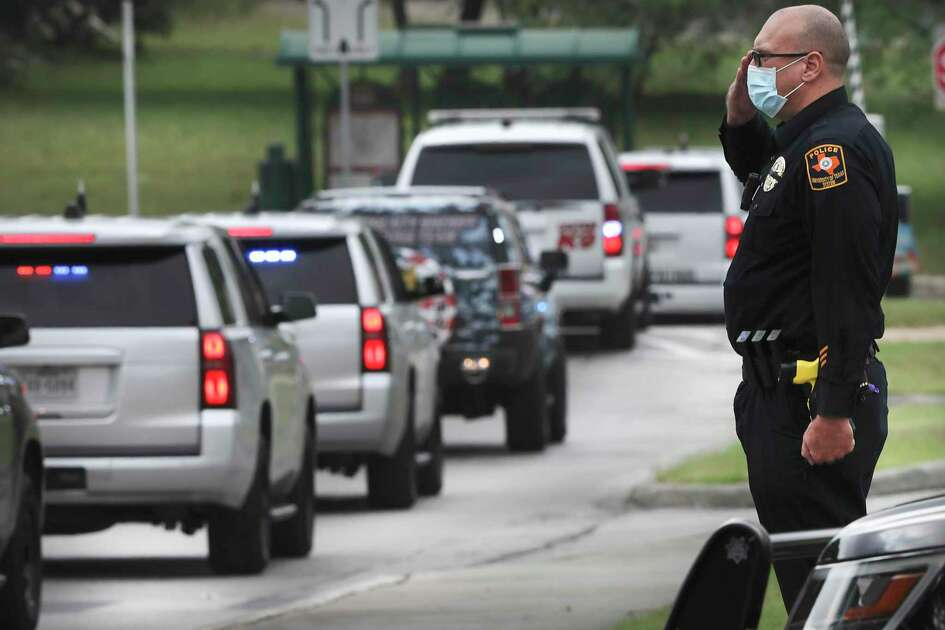 An officer from the University of Texas System Police salutes the funeral procession for Bexar County Sheriff's Deputy Timothy De La Fuente on May 4. De La Fuente was the first employee at the Bexar County jail to die with novel coronavirus. The death toll in Bexar County now stands at 380.