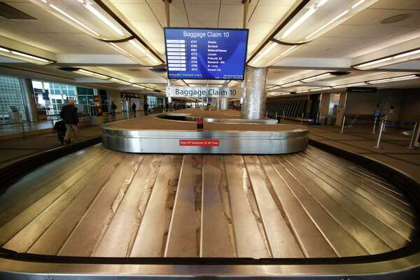 In this March 20, 2020, photo, an empty baggage carousel spins in Denver International Airport. When faced with an existential threat like the coronavirus, what direction do you take your company? American Airlines has increased flights and filled seats while other airlines are taking a more conservative route.