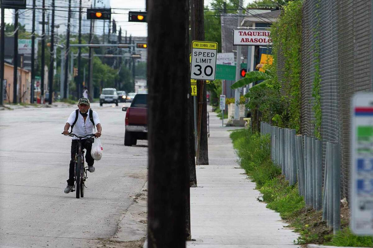 A man cycles down Hogan Street on Tuesday, Aug. 4, 2020, in the Near Northside neighborhood of Houston. The City of Houston is voting Wednesday on a new