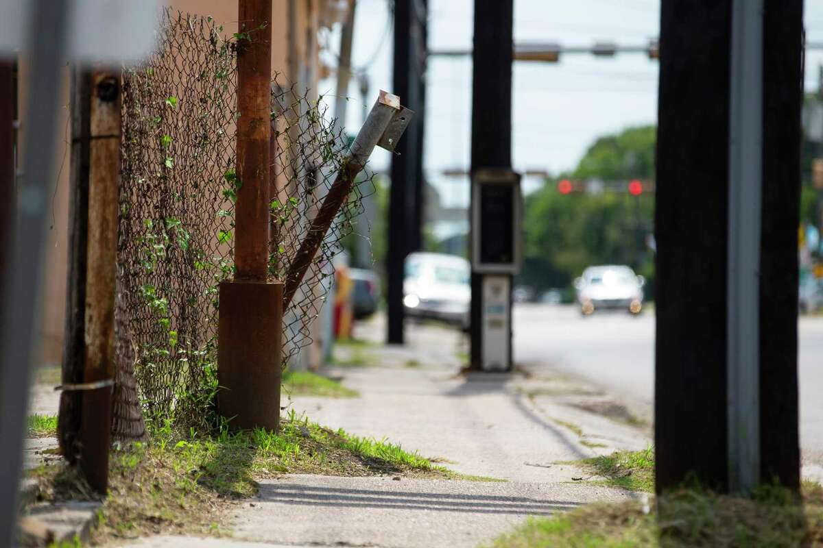 A piece of metal fencing leans into the sidewalk along the south side of Hogan Street on Tuesday, Aug. 4, 2020, in the Near Northside neighborhood of Houston.