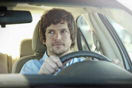 Young man behind the wheel of his car, glancing into rearview mirror