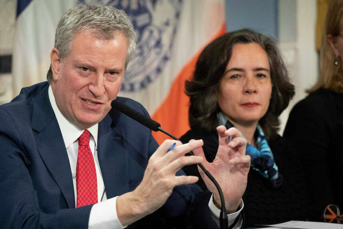 FILE - In this Wednesday, Feb. 26, 2020, file photo, Mayor Bill de Blasio, left, is shown with Dr. Oxiris Barbot, commissioner of the New York City Department of Health and Mental Hygiene, in New York. New York City abruptly replaced Barbot, its top public health official, Tuesday, Aug. 4, 2020, at a key point in its fight to keep the coronavirus from surging again. (AP Photo/Mark Lennihan, File)