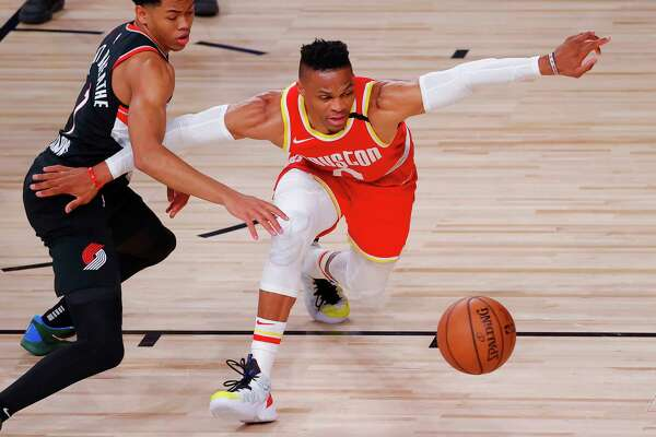 Anfernee Simons, left, of the Portland Trail Blazers knocks the ball away from Russell Westbrook, right, of the Houston Rockets during the first half of an NBA basketball game Tuesday, Aug. 4, 2020, in Lake Buena Vista, Fla. (Kevin C. Cox/Pool Photo via AP)