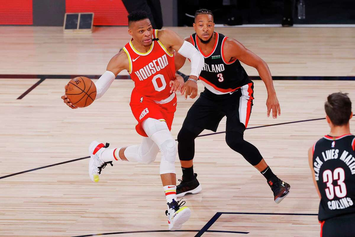 Russell Westbrook, left, of the Houston Rockets drives to the basket against CJ McCollum, right, of the Portland Trail Blazers during the first half of an NBA basketball game Tuesday, Aug. 4, 2020, in Lake Buena Vista, Fla. (Kevin C. Cox/Pool Photo via AP)
